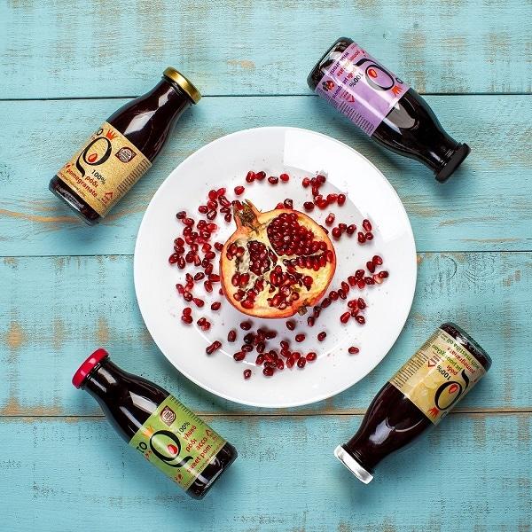 Verschiedene Flaschen Granatapfelsaft auf dem Tisch und Granatapfelkerne auf einem Teller